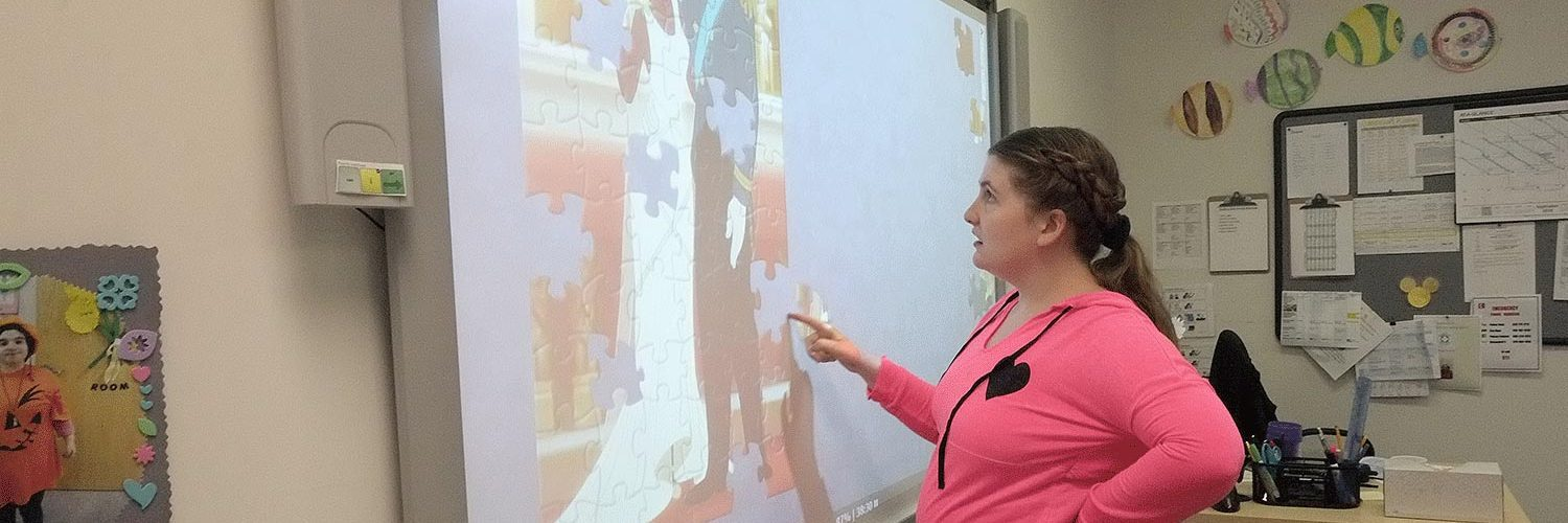 woman doing puzzle on a smart board