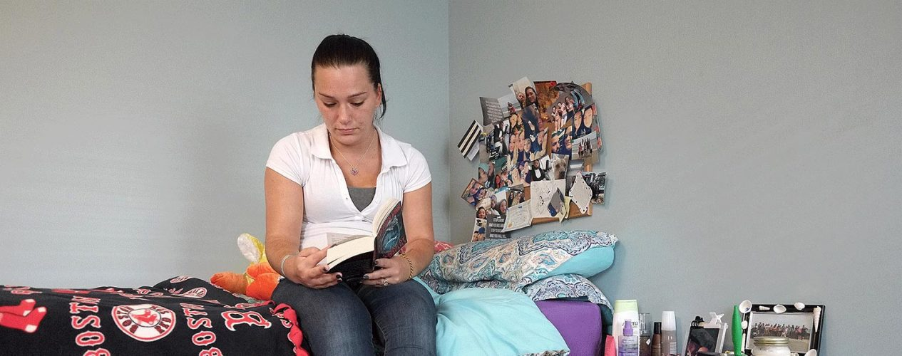 woman in recovery services program reading on her bed